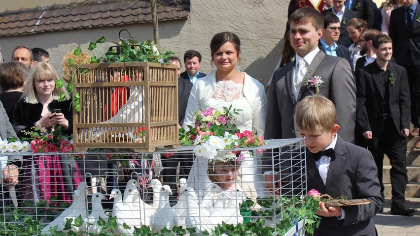 """Die Hochzeitsglocken der Pfarrkirche St. Peter und Paul in Pilsach läuteten für Tanja Frisch aus Richtheim und Dominik Liedlbier aus Ungenricht. Pfarrer Martin Fuchs hielt die Hochzeitsmesse, die von der Gruppe """"Viva La Lieda"""" gestaltet wurde. Danach musste das Brautpaar ein langes Spalier durchschreiten. Es gratulierten die Kirwaleit Konzuf, die Freiwillige Feuerwehr Loderbach und der Brieftaubenverein Berg, wo die Braut aktiv ist, sowie der Jungzüchterclub Neumarkt-Regensburg. Anschließend wurde das Paar von einem Bekannten mit seinem Oldtimer VW Bulli zum Berggasthof Sammüller gefahren, wo es mit vielen Gästen zünftig feierte. Die 28-jährige Hausverwalterin die bei einer Immobilienfirma in Altdorf arbeitet und der ein Jahr ältere Landwirtschaftsmeister haben sich vor zehn Jahren durch Freunde kennengelernt und am 22. Februar dieses Jahres, am 10. Jahrestag, standesamtlich geheiratet. Da Paar lebt künftig auf dem Bauernhof in Ungenricht, wo sie sich im Elternhaus des Bräutigams eine Wohnung eingerichtet haben. miku"""