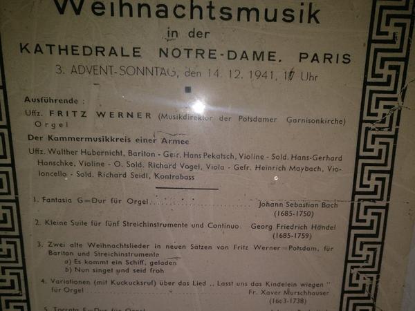 Dieses Plakat aus der Besatzungszeit lag hinter der Orgel. Wie Denny Wilke im Bild festhält, wurde zum Orgelkonzert 1941 mit Hakenkreuz eingeladen, unterzeichnet vom Kommandanten von Großparis.
