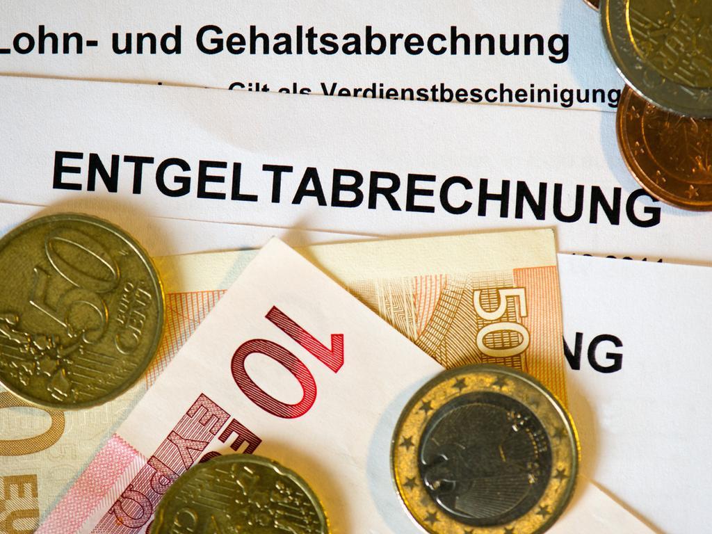 ARCHIV - ILLUSTRATION - 31.01.2013, Sachsen, Dresden: Auf Lohn- und Gehaltsabrechnungen (Entgeltabrechnungen) liegen Euromünzen und Eurogeldscheine. Die Führungskräfte deutscher Unternehmen sehen das Konzept eines bedingungslosen Grundeinkommens überwiegend kritisch. (zu dpa «Führungskräfte sehen bedingungsloses Grundeinkommen meist kritisch» vom 29.04.2018) Foto: Arno Burgi/dpa-Zentralbild/dpa +++(c) dpa - Bildfunk+++ | Verwendung weltweit