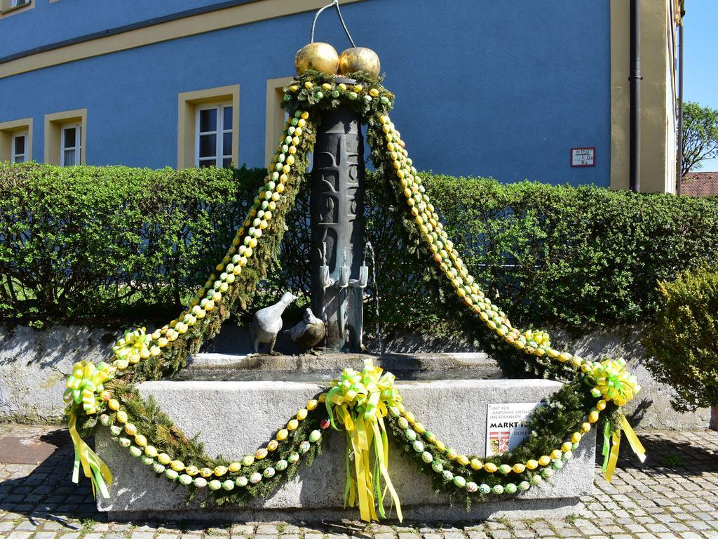 Der Osterbrunnen am ehemaligen Schulhaus in Igensdorf erstrahlt in fröhlichen Frühlingsfarben.