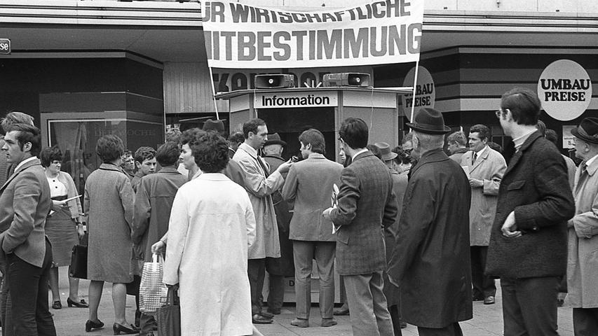 """Jungsozialisten bieten Information: An ihrem Stand in der Fußgängerzone Pfannenschmiedsgasse holten sich viele Passanten Schriften über die DGB-Forderung zum 1. Mai: """"Für wirtschaftliche Mitbestimmung!"""" Juso-Vorsitzender Horst Schmidtbauer (im hellen Mantel mit Mikrofon) fragt die Bürger nach ihrer Meinung. Hier geht es zum Artikel vom 2. Mai 1969: Nürnberger Jusos unterstützen DGB."""