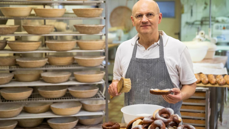 Arnd Erbel führt seine Dachsbacher Bäckerei in der zwölften Generation. Hier salzt er gerade Brezen, viele Backwaren liefert der Handwerksmeister nach Nürnberg. Die Kleinen der Branche kommen gegen die großen Backfabriken nicht an, sagt er.