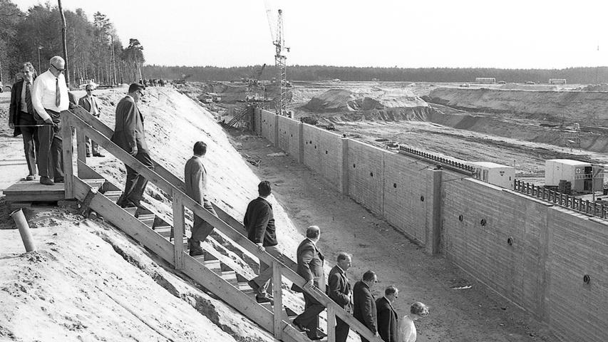 Im Gänsemarsch steigen die Gäste zur Talsohle der Hafeneinfahrt hinab, deren Betonwände zum Teil schon stehen. Dahinter rollen die Bagger und Raupenfahrzeuge ohne Unterlaß.  Hier geht es zum Artikel vom 6. Mai 1969: Bald Schiffe in Sicht