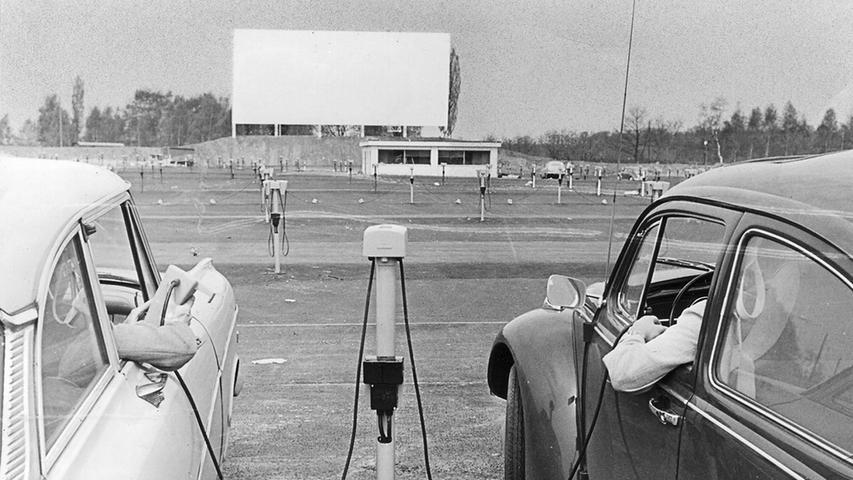 Zwei Autofahrer testen den Kino-Logenplatz und die Lautsprecher, die von der Zapfsäule in den Wagen geholt und dort in Betrieb gesetzt werden. Im Hintergrund die Bildwand.  Hier geht es zum Artikel vom 7. Mai 1969: Logenplatz im Auto