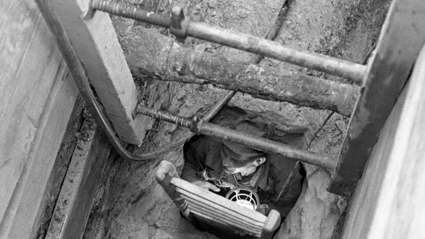"""So sieht die Baustelle in der Bauvereinstraße aus: durch ein schmales Loch klettert der Arbeiter (rechts) in den unterirdischen Tunnel, der 2,50 Meter hoch und etwa einen Meter breit ist, Der """"Fluchtgang"""" soll mehrere hundert Meter lang sein.  Hier geht es zum Artikel vom 10. Mai 1969: Fluchtweg oder Wasserschacht?"""