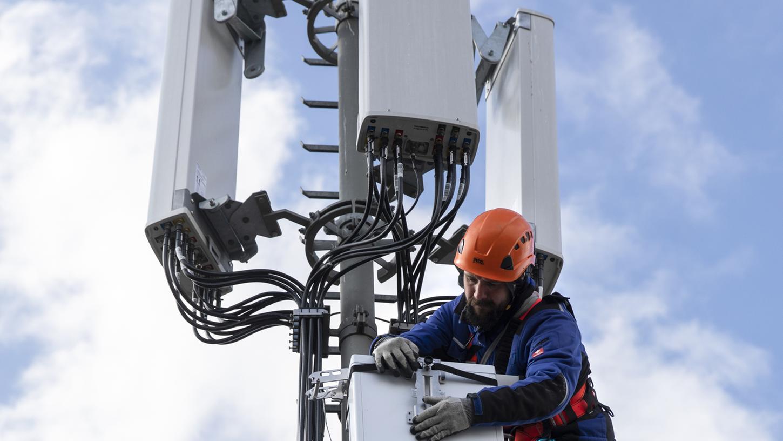 Foto aus der Schweiz: Ein Techniker installiert eine Antenne für das 5G-Funknetz auf einem Hausdach.
