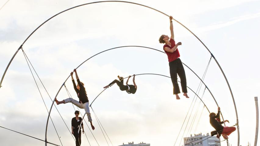 """Die Hektik des Alltags: Menschengedränge, Autohupen, Straßenlärm und mittendrin schwebende, fast schwerelose Akrobatinnen. Die französische Künstlerin und Gründerin der Compagnie """"Rhizome"""", Chloé Moglia, ist bekannt für ihre entschleunigten Arbeiten mit artistischen Mitteln. Dafür konzipierte sie in den letzten Jahren vermehrt Stücke für den öffentlichen Raum, die eine Nähe zu den Zuschauenden schaffen. Zu erleben ist sie vom 24. bis 26. Mai in Erlangen."""