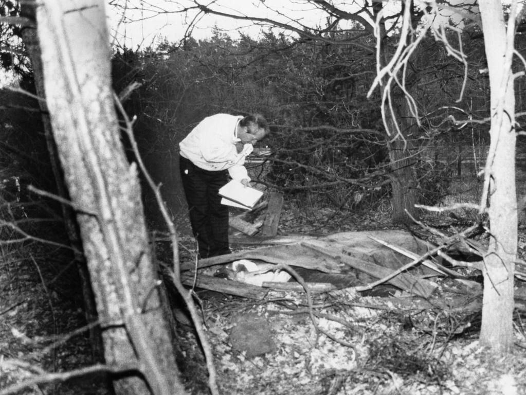 Ein Ermittler erkundet den Fundort der Leichen im Wald. Der Täter hatte seine Opfer mit Dachpappe zugedeckt.