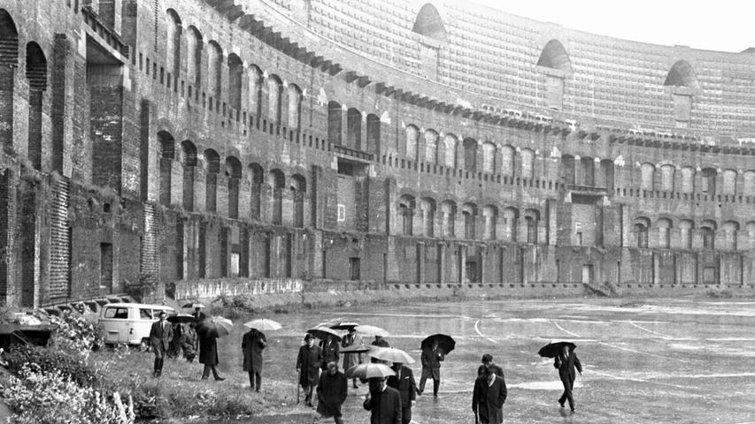 """Der Besichtigungskommission wird rein auch schon gar nichts erspart. Im Innenhof kann sie richtiggehend """"kneippen"""". Schirme nützen herzlich wenig gegen den niederprasselnden Regen, wenn sich auf dem Betonboden das Wasser knöcheltief staut.  Hier geht es zum Artikel vom 6. Juni 1969:"""