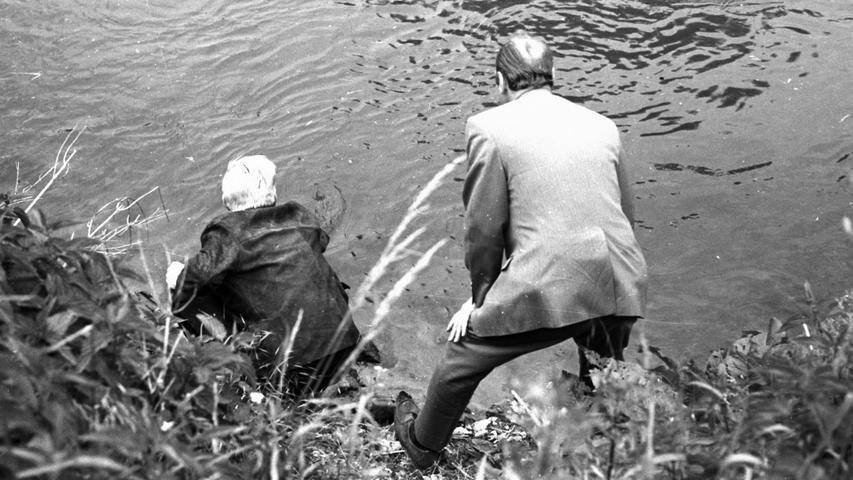 """Einer der Hauptakteure der """"Schränker-Bande"""", der 20jährige Hans Z., versucht hier im Beisein eines Kriminalbeamten, das in der Pegnitz beim Hainberg versenkte Schweißgerät herauszufischen. Unweit von dieser Stelle schimmert dicht unter der Wasseroberfläche ein Tresor, den Hans Z. einmal dort versenkt hat. Aus ihm waren den Tätern 5.000 DM in die Hände gefallen.  Hier geht es zum Artikel vom 7. Juni 1969: Türdichtung wurde zum Verhängnis"""