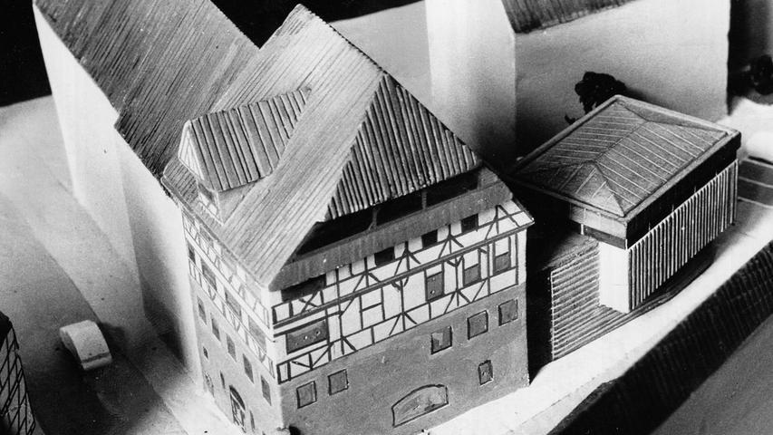 """Wie das Hornberger Schießen endete gestern im Bauausschuß die jüngste Runde im Tauziehen um den Dürer-Haus-Anbau. Lange standen die Stadtväter vor dem farbigen Modell und wiegten bedenklich die Häupter. Sie erfanden manch' originelle Bezeichnung wie """"Edelgarage"""" oder """"KunstTrafo"""" für das Gebäude, das der Baukunstbeirat mit dem Attribut """"ausgezeichnet"""" versehen hat. Aber einig wurden sie sich nicht einmal über die Notwendigkeit eines solchen Anhängsels, geschweige denn über dessen Aussehen.  <a href="""