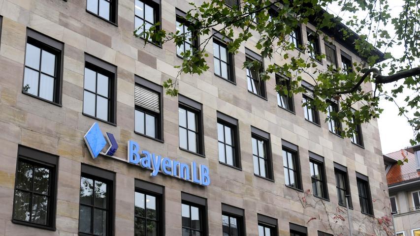 Der Nürnberger Standort der Bayerischen Landesbank liegt nicht nur direkt gegenüber der Sparkasse am Lorenzer Platz, die BayernLB gehört auch der gleichen Finanzgruppe an wie der Nachbar mit dem roten Logo: Landesbanken zählen wie die Sparkassen zum öffentlich-rechtlichen Sektor. Die genossenschaftlichen sowie die privaten Banken bilden weitere zwei der zusammen drei Säulen des deutschen Finanzsystems. Die Bayern LB hat ihren Hauptsitz in München. In Nürnberg betreibt die Bank ihr Kompetenzzentrum für Sorten und Edelmetalle.
