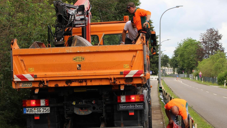 Der Lkw hat Erde geladen. Mitarbeiter des Forstbetriebs Allersberg der Bayerischen Staatsforsten verteilen sie auf der Folie, um sie zu beschweren.
