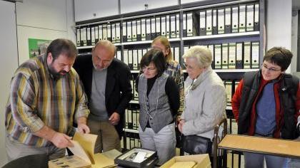 Stadtarchiv-Mitarbeiter Thomas Dütsch (links) zeigt den interessierten Gästen alte Foto-Negative. Die umfangreichen Bestände sind topografisch, also nach den Adressen, geordnet.