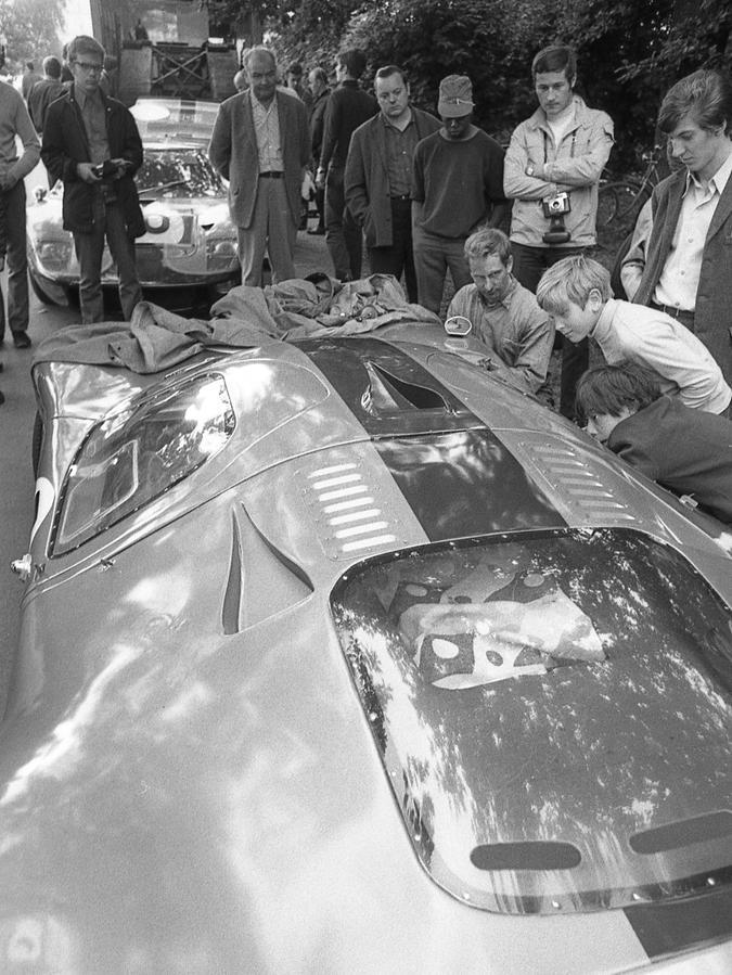 """Kaum waren die großen """"Renner"""" angekommen, wurden sie auch schon von der Jugend staunend umlagert und begutachtet. Hier steht der Ford Mirage des englischen Millionärssohnes Mike Hailwood im Mittelpunkt des Interesses."""