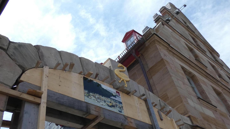 Ein goldener Schwan ziert wieder den Mittelstein des neu errichteten Torbogens, den im Moment noch eine Holzkonstruktion stützt. Auf dem Stein soll künftig – wie früher – eine Muschel aus Sandstein stehen.