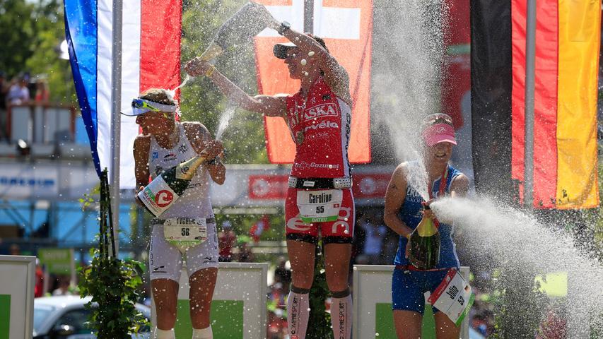 Caroline Steffen (SUI, in der Bildmitte) feiert ihren Sieg 2013 in 8:45:04 mit einer Sektdusche.
