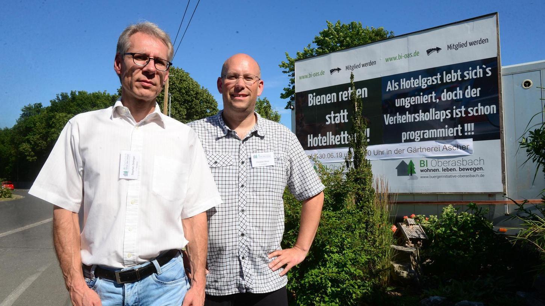 Vor dem großen Protestschild an der Oberasbacher Jahnstraße stehen Stephan Zeilinger (links) und Christian Bloß. Die beiden Sprecher der Bürgerinitiative wünschen sich eine offene Debatte über das Hotelprojekt in ihrer Stadt.
