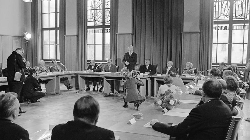 """Zweite Sitzung des Dürer-Jahr-Kuratoriums im Rathaussaal: Bundeskanzler Kiesinger als Vorsitzender muß zu Beginn seiner Ansprache das """"Blitzgewitter"""" der Fotografen über sich ergehen lassen. Arbeitsminister Dr. Pirkl, Stadtrat Dr. Glaser, OBM Dr. Urschlechter, Bürgermeister Haas und Bundesminister Käte Strobet (v. l. n. r. am Präsidium) lauschen wie die übrigen Mitglieder des Gremiums aufmerksam seiner Rede. Auf dem Bild sind außerdem (ganz links) Richard Stücklen, Dr. Eberhard und Konsul Dr. Grundig zu erkennen.  Hier geht es zum Artikel vom 5. Juli 1969:"""