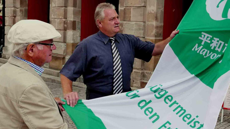 Pfarrer i.R. Hans-Jörg Schmid (l. mit Bürgermeister Klaus Meier beim Hissen der