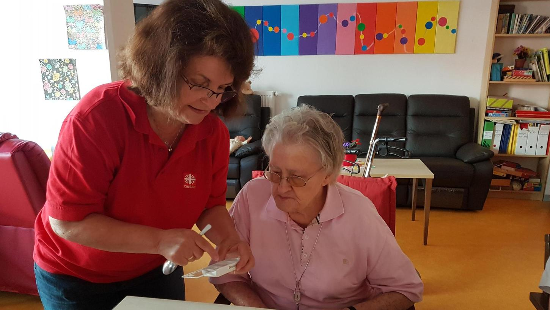 Die Nürnberger Krankenschwester Ursula Huh (links) gibt der Demenz-WG-Bewohnerin Anneliese Stellwag Medikamente. Tochter und Schwiegersohn der Seniorin fürchten um die Zukunft der Einrichtung.