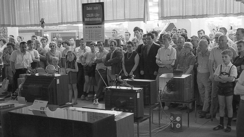 Zuschauer in der Radio- und Fernsehableitung eines Kaufhauses in der Innenstadt: die Kunden verfolgen gespannt den Start des Raumschiffes Apollo II, das die drei amerikanischen Astronauten samt ihrer Mondfähre pünktlich auf die Minute ins All hinausträgt.  Hier geht es zum Artikel vom 16. Juli 1969: Mondflug hält die Stadt in Spannung