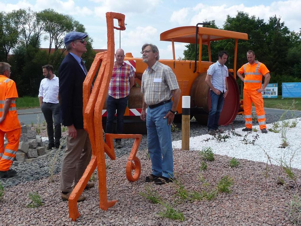 Ganz in Orange: Ein stilisierter Bauarbeiter mit Schubkarre ist der Beitrag des Ammerndorfer Künstlers Arnold Bögelein (vorne rechts) zu der Dekoration des Kreisels an der östlichen Ortseinfahrt der Gemeinde.