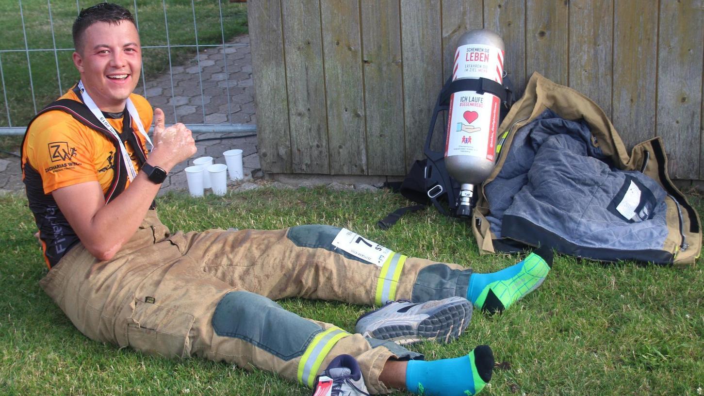 """Nach 55:58 äußerst schweißtreibenden Minuten im Ziel auf dem Sportgelände des SV Unterwurmbach: der """"Feuerwehrläufer"""" aus Zirndorf braucht erst mal viel Wasser."""