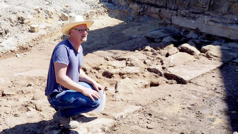 Archäologe Marco Goldhausen kniet bei einem Stück der alten Ringmauer aus dem 15. Jahrhundert und erläutert, was es mit den Buckelquadern auf sich hat.