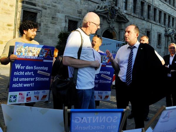 Den Auftritt von Bayerns Wirtschaftsminister Hubert Aiwanger (FW, Bildmitte) beim IHK-Kammergespräch in Nürnberg nutzten Mitglieder der Sonntagsallianz, um gegen dessen Pläne, den Sonntagsschutz zu lockern, zu demonstrieren.