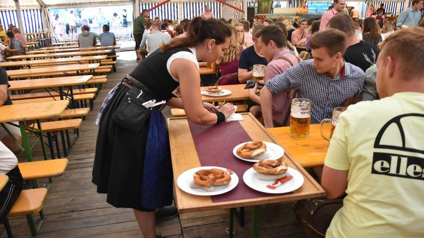 Die Kellner haben in den ersten Minuten gut zu tun, um die zahlreichen Gäste mit Speis und Trank zu versorgen. Sie tragen den ganzen Vormittag schwere Tabletts mit Speisen und bis zu vierzehn Bierkrüge auf einmal.