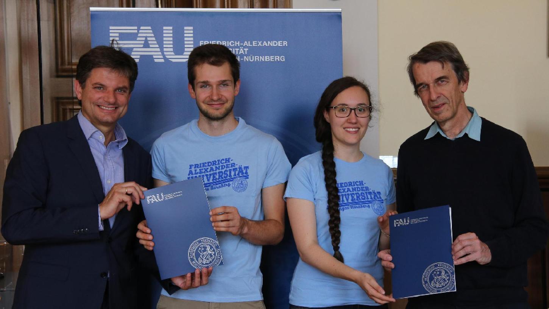 Uni-Präsident Joachim Hornegger (l.) gratulierte den Studierenden, die die Solaranlage selbst montierten. Martin Hundhausen (r.) übergab die Anlage jetzt der Uni.