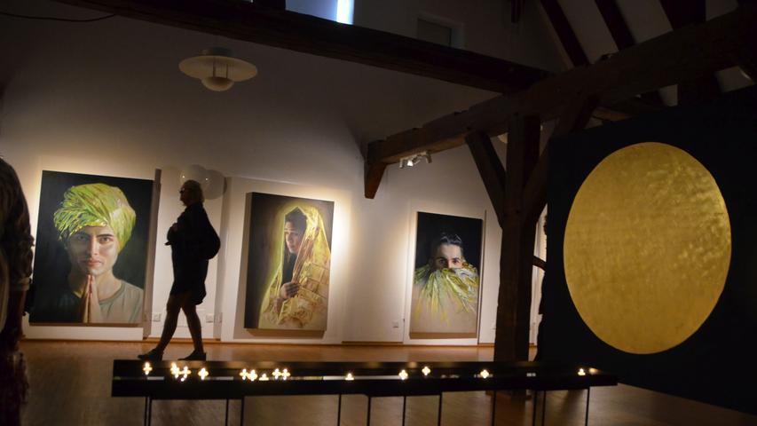 """Geboren wurde Babette Brühl in der Lüneburger Heide. Seit ihrem Studium in Hannover und Stuttgart, arbeitet sie als freiberufliche Designerin und konzipiert und gestaltet Ideen mit hoher gesellschaftlicher Relevanz. Das spiegelt sich auch in ihrer Arbeit """"Kinder eines Goldenen Zeitalters"""". Auf großen Ölgemälden sind Kinder verschiedener Nationalität abgebildet, scheinbar mit goldenen Roben bekleidet und wie Heilige oder Herrscher anmutend. Näher betrachtet entpuppen sich die Roben als Rettungsdecken, wie sie in der Seenotrettung eingesetzt werden."""