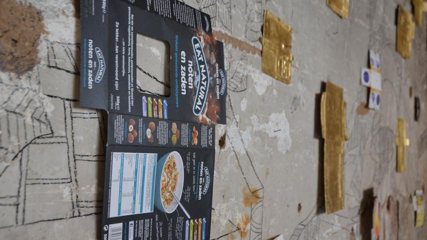 """...Bei ortung 11. zeigt sie ihr Werk """"Commercial Crosses"""", für das sie seit 2013 hunderte Verpackungen gesammelt, geöffnet und deren Innenseiten vergoldet hat. Die dabei entstandenen kreuzförmigen Goldobjekte sind wie ein Tagebuch des eigenen Konsumverhaltens."""