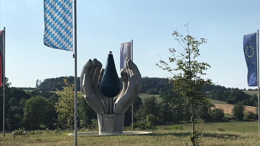 Und noch ein Kunstbrunnen: Dieser steht in der Mitte des Kreisverkehrs zwischen Neustadt an der Aisch und Diespeck. Seine Gestaltung mit Händen, die einen Wassertropfen halten, hat nicht nur zufällig etwas mit dem in unmittelbarer Nachbarschaft des Kreisverkehrs angesiedelten Mineralwasserabfüller zu tun.
