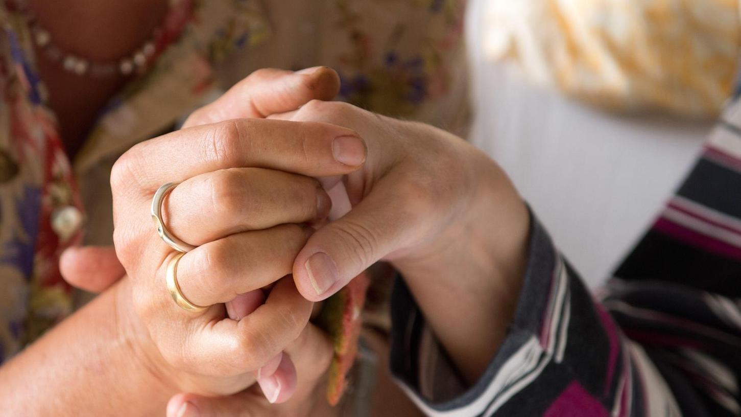Wichtiger Beistand: Eine Therapeutin hält in einem Hospiz die Hand einer todkranken Bewohnerin.