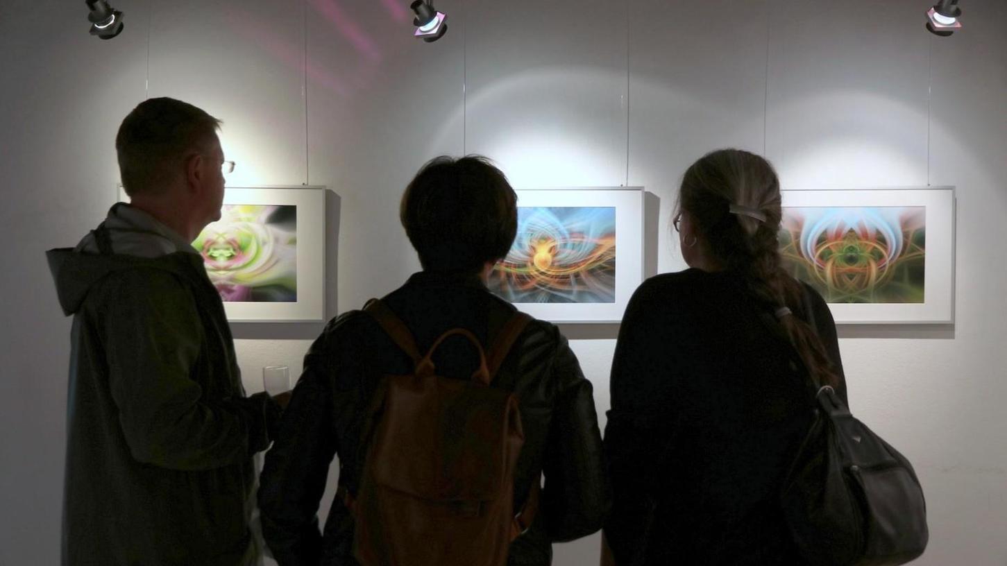 Fasziniert betrachten die Besucher der Vernissage die Fotografien, die fast wie Malereien anmuten.
