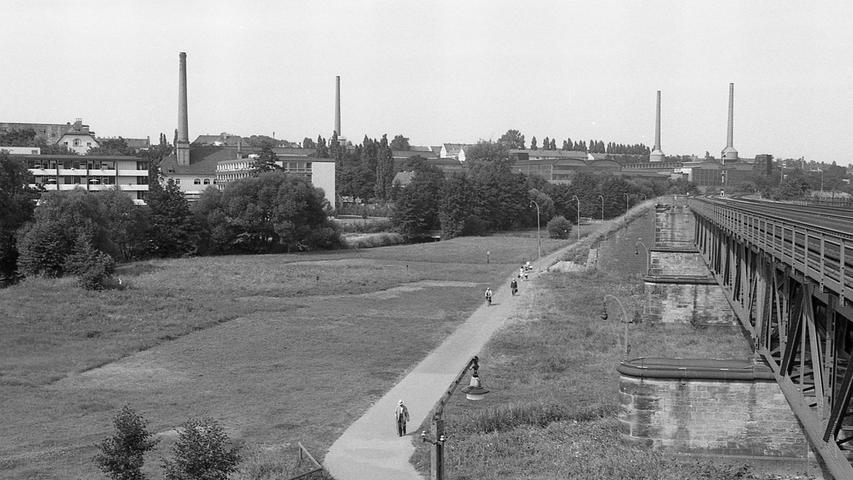 Ein Blick vom damaligen Pulversee (heute Freibad Bayern 07) aus auf das nordöstliche Pegnitztal im August 1969. Rechts die Eisenbahnbrücke der Bahnstrecke Richtung Bayreuth.Im Hintergrund der Turm des Sebastianspitals, daneben das Tafelwerk mit seinen Schlöten.  Heute befindet sich der Fußweg eine Etage höher auf der Bahnbrücke (gegenüberliegende Seite).