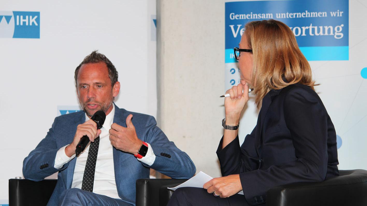 Umweltminister Thorsten Glauber aus Pinzberg bei der Vollersammlung der Industrie- und Handelskammer zusammen mit der Moderatorin der Veranstaltung, Anja-Maria Meister.