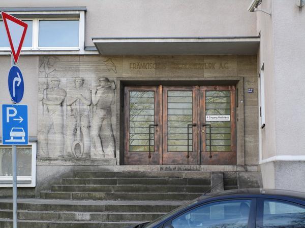 Am früheren Hauptportal mit seinem auffälligen Reliefschmuck und den originalen Schwingtüren scheint die Zeit stehengeblieben zu sein.