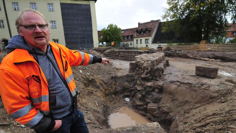 Marco Goldhausen, Leiter des Archäologen-Teams, das seit Juli 2019 den Untergrund des ehemaligen Rathaus-Trakts in Herzogenaurach untersuchte, deutet auf die verschiedenen Schichten des Fundaments von Ringmauer und Bergfried.