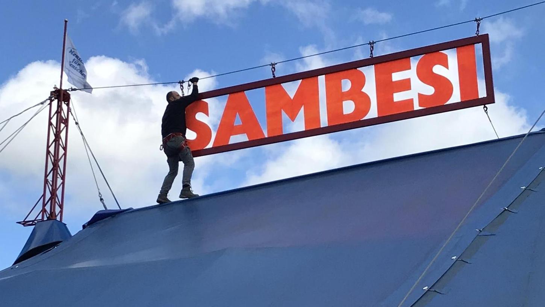 Eine heftige Windböe hatte des große Sambesi-Schild aus der Befestigung gerissen. Ein mutiger Mitarbeiter wagte sich in luftige Höhe und klinkte den Haken wieder ein.