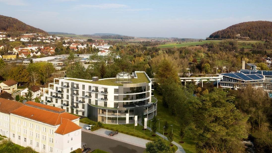 """Zwischen dem ehemaligen RAD-Lager (links) und der per """"Bademantel-Gang"""" angebundenen Therme (rechts) soll das neue Hotel mit rund 200 Betten entstehen."""