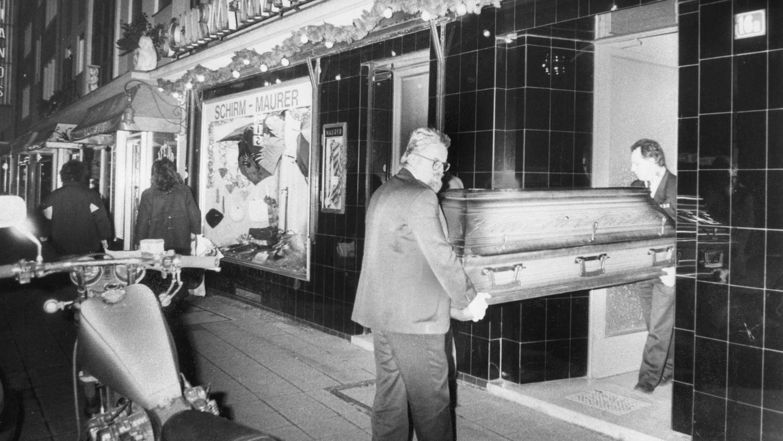 Bestatter tragen im Dezember 1990 einen Sarg aus dem alteingesessenen Schirm- und Hutladen in der Tafelfeldstraße. Dort war die 69 Jahre alte Inhaberin Liselotte M. ermordet worden. Wer der Täter war, konnte bis heute nicht geklärt werden.