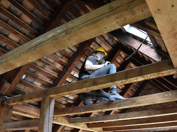 Ganz oben im soliden Dachgebälk entfernt ein Helfer mit Atemschutzmaske gegen den Staub Bretter, aus denen später neue Bauten entstehen sollen.