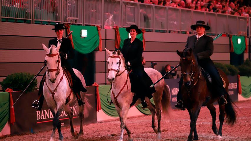 Drei Reiterinnen im spanischen Stil mit Garrocha, einem Stock, mit dem bei der Rinderarbeit einzelne Tiere von der Herde getrennt werden. Dafür muss mit einer Hand geritten werden - das Pferd muss also besonders fein auf Schenkel- und Gewichtshilfen reagieren. Die Reitweise findet in der Sportlandschaft inzwischen unter dem Stichwort
