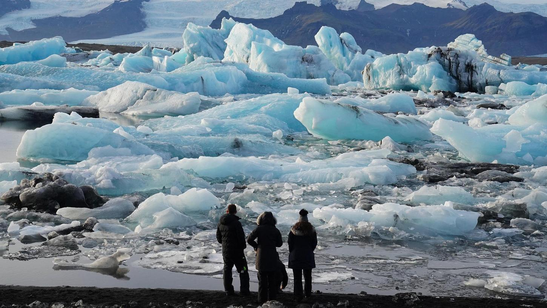 Der Klimawandel schreitet sichtbar voran, seine Folgen sind schon jetzt dramatisch, wie auf unserem Bild zu sehen ist: Hier stehen Touristen in Island vor Eisbergen in der Gletscherlagune Jökulsarlon im Süden des Landes.