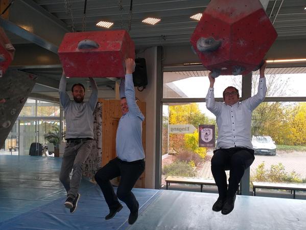"""Simon Brünner, Norbert Stumpf und Florian Janik (v. li.) zeigten sich erfreut über die Boulderhallenpläne """"Blockhelden 2.0"""" in Bubenreuth und testeten die grauen Henkel."""