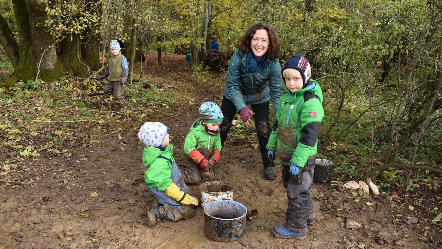 Es ist still in diesem Teil des Waldes, obwohl dort gut zehn Kinder am Spielen sind. Nur ab und zu knackt ein Ast, wenn die Kinder beim Transportieren ihrer mit Wasser und Matsch gefüllten Kochtöpfe zum großen Baumstamm balancieren.