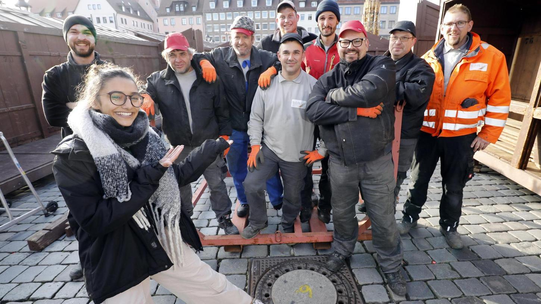 Hier liegt ihr neuer Arbeitsplatz: Benigna Munsi begrüßt spontan die Männer vom Servicebetrieb Öffentlicher Raum, die auf dem Hauptmarkt die Christkindles-Buden aufbauen.